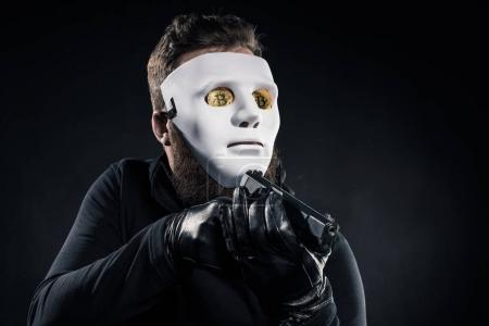 Male criminal in mask and bitcoins on eyes aiming with gun