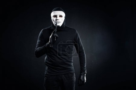 Robber in mask and balaclava holding gun