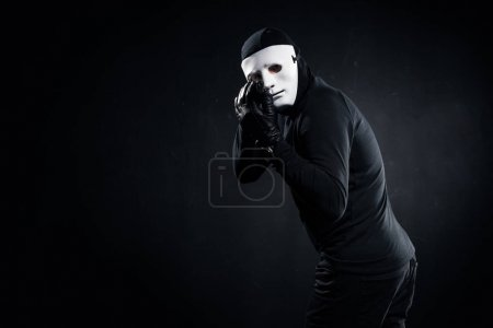 Male robber in mask aiming with gun on black