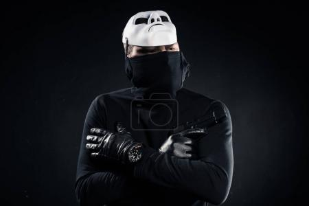 Thief in black balaclava and white mask holding gun in folded arms on black