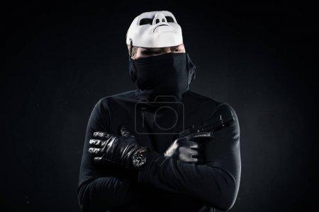Voleur en cagoule noire et masque blanc tenant le pistolet dans les bras croisés sur fond noir