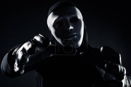 Man in mask reaching to the camera with his hands...