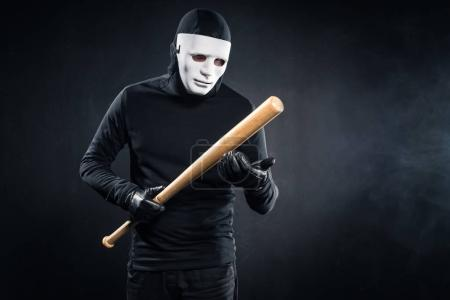 Criminal in mask and balaclava holding baseball bat