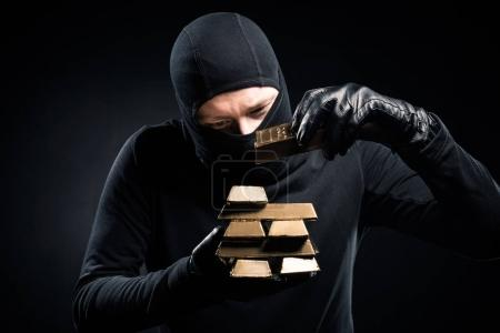 Robber in balaclava stacking gold bullions in his hands