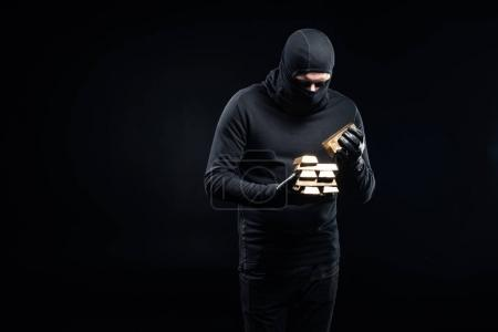 Thief in balaclava stacking gold ingots in his hands