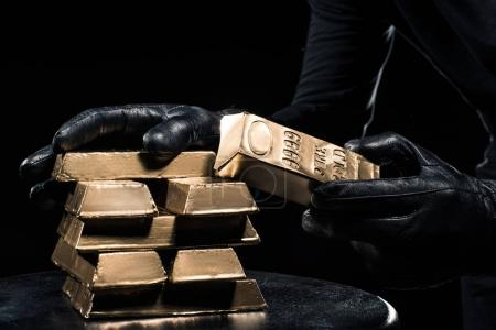 Close-up view of golden bars in hands of thief