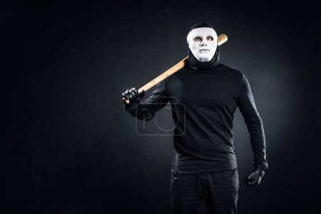 Burglar in mask and balaclava holding baseball bat