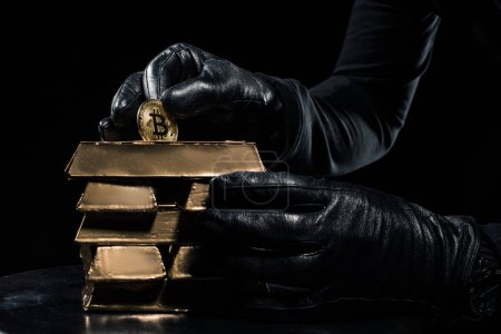 Close-up view of golden bars and bitcoin in hands of thief