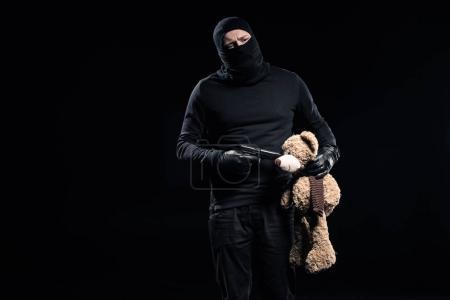 Photo for Burglar in balaclava holding gun and teddy bear - Royalty Free Image