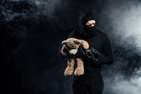 Kidnapper in balaclava holding gun and teddy bear