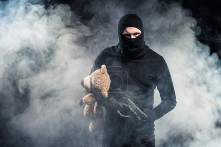 Criminal in balaclava holding gun and teddy bear in clouds of smoke