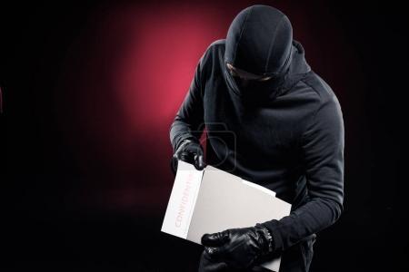 Burglar in balaclava holding confidential documents