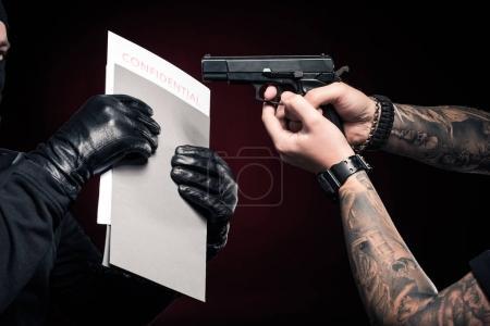 Photo pour Homme armé protégeant ses papiers confidentiels contre le voleur - image libre de droit
