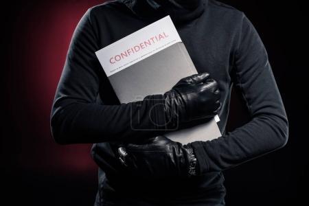 Photo pour Recadrée vue pénal tenant le dossier avec des documents confidentiels - image libre de droit