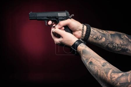 Close-up view of male hands aiming with gun