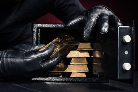 Cropped view of thief stealing gold ingots from safe