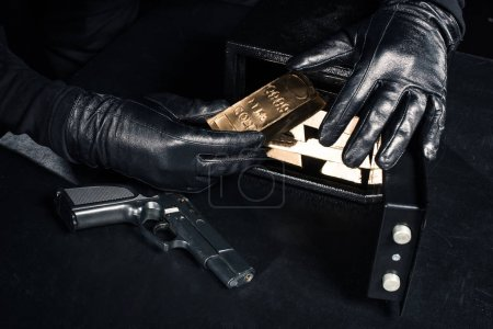 Close-up view of robber with gun taking gold bars from safe