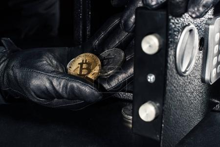 Thief hand stealing golden bitcoin from safe