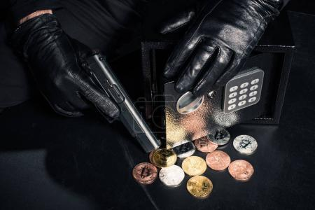 Close-up view of robber with gun stealing bitcoin from safe