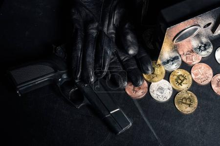 Black gloves and gun by open safe with bitcoin