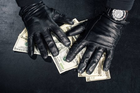 Male hands in black gloves grabbing dollars