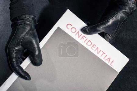 Close-up view of criminal holding folder with confidential documents