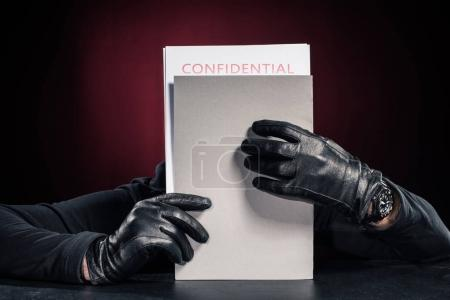 Criminal in black gloves holding confidential documents