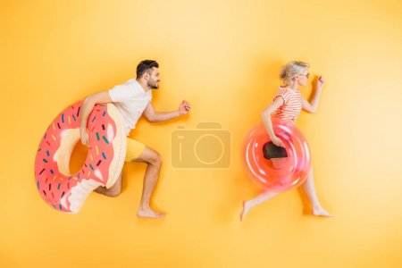 happy young couple holding inflatable swimming rings on yellow