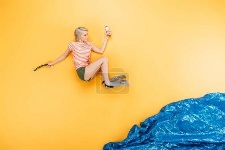 beautiful young woman in flippers jumping in imagine sea on yellow, summer vacation concept