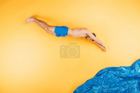 handsome young man in shorts diving in imagine sea on yellow