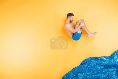 handsome young man in shorts jumping in imagine sea on yellow