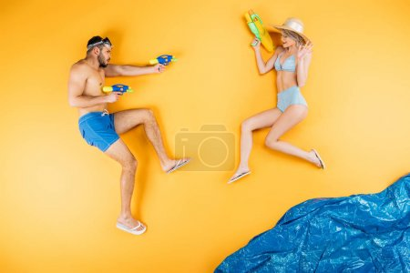 young couple in swimwear playing with water guns on imagine beach, summer vacation concept