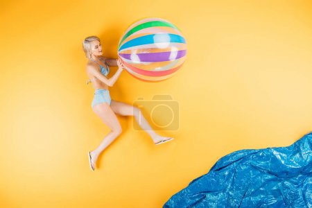 beautiful young woman in swimsuit and flip flops holding inflatable ball on imagine beach