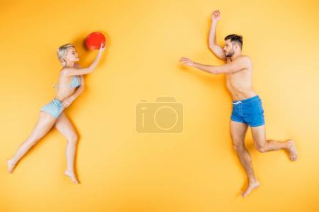 young barefoot couple in swimwear playing with flying disk on yellow, summer vacation concept