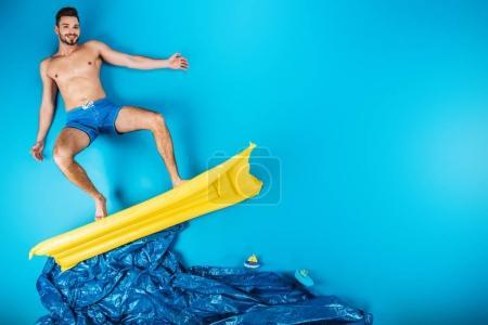 Foto de Atractivo joven en shorts sonriendo a la cámara mientras está parado sobre un colchón inflable en azul - Imagen libre de derechos