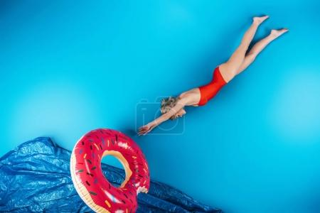 Photo for Girl with swimming ring diving in imagine sea on blue, summer vacation concept - Royalty Free Image