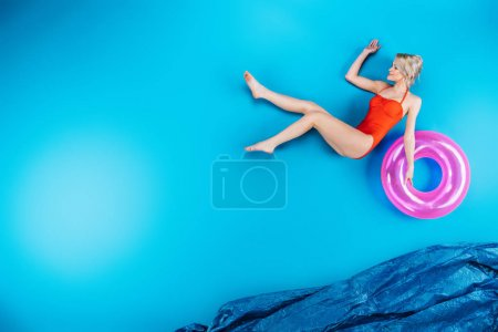 beautiful young woman in swimsuit holding inflatable ring on blue