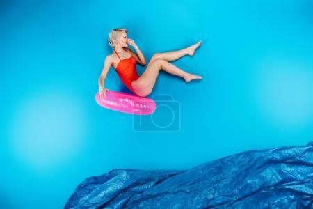 beautiful young woman in swimsuit holding inflatable ring and jumping in imagine sea on blue