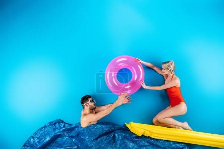 Photo for Young couple having fun with beach items in imagine sea on blue - Royalty Free Image