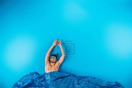 happy young man in swimming mask raising hands from imagine waves on blue