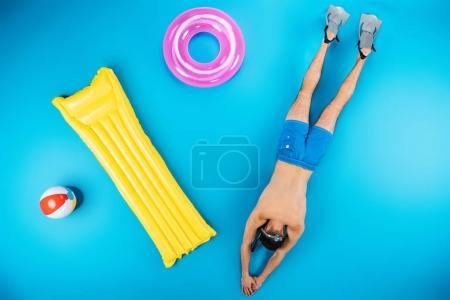 Photo pour Vue de dessus du jeune homme plongeant avec des palmes et des articles de plage sur bleu - image libre de droit