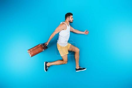 Photo for Full length view of handsome young man holding suitcase and running on blue - Royalty Free Image