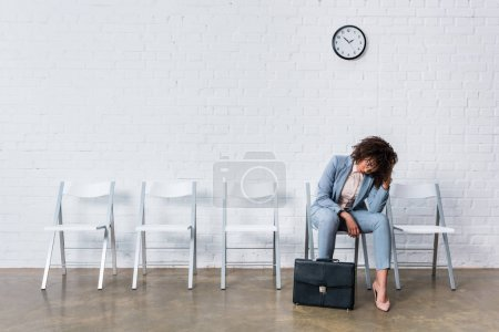 Tired female candidate with briefcase waiting for interview