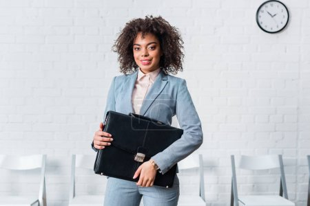 Photo for African american businesswoman in suit holding briefcase - Royalty Free Image