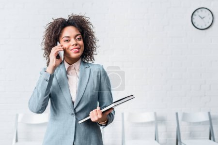 Young businesswoman with papers talking on the phone
