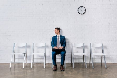 Curious man with briefcase waiting for interview while sitting on chair