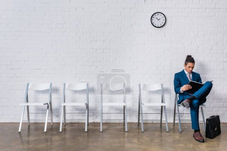 Man reading papers while sitting on chair