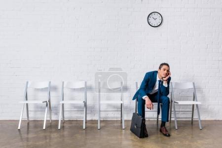 Homme s'ennuie avec mallette assis sur une chaise et d'attendre