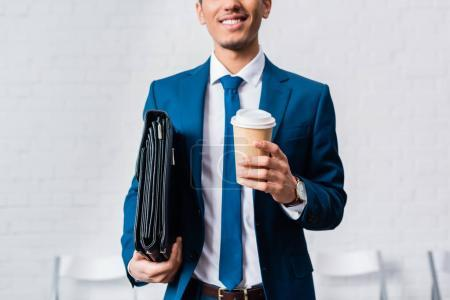 Smiling businessman holding briefcase and coffee cup