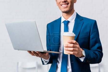 African american businessman holding laptop and coffee cup